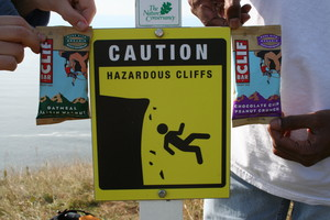 Sign That Reads Hazardous Cliffs with Sam and Elyssia Holding Up Two Cliff Bars