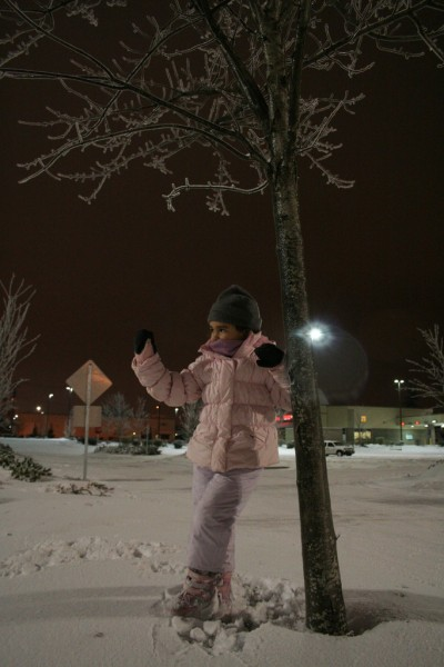 Allie Standing by a Tree in the Snow Waving at Grandpa