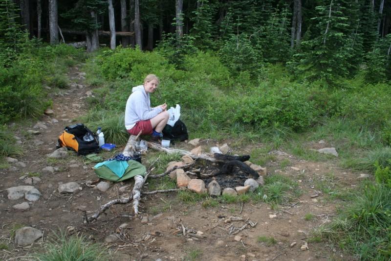 Tasha sitting on a log by a firepit eating lunch