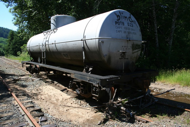 Old graffittied tanker car sitting on a parallel track
