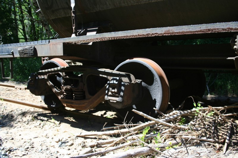 Debris piled up by the wheels of the tanker car