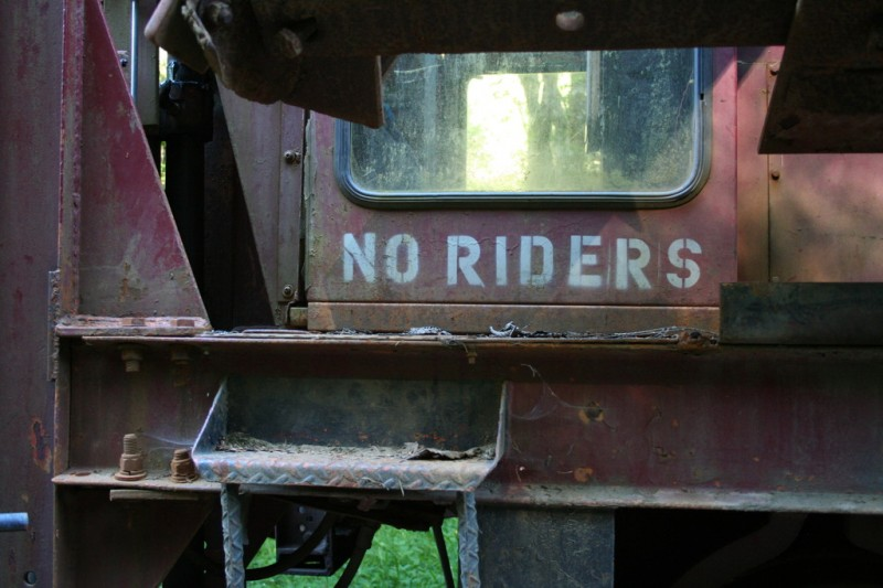 Stenciled onto the ballast tamper: NO RIDERS