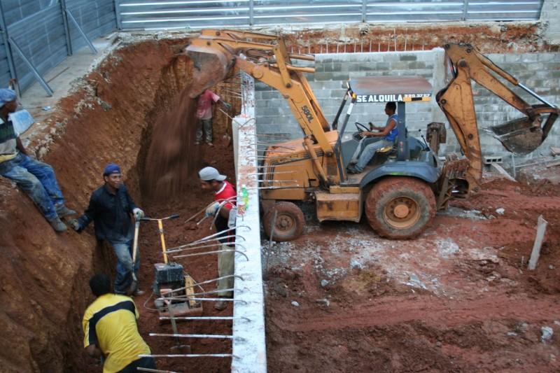 Backhoe Dumping Dirt Behind the Wall