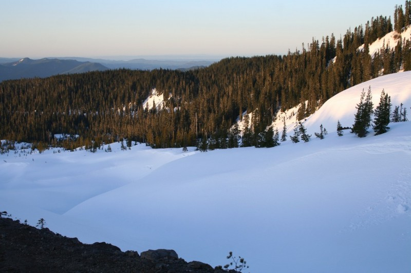 snowy scene just above the treeline with distant mountains in the background and a rocky outcropping in the foreground