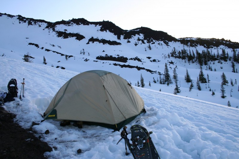 tent pitched in flat space dug out of the snowy slope with snow shoes and poles in the foreground