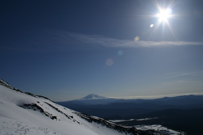 mt adams and the sun in the distance with the slope of mt st helens in the foreground