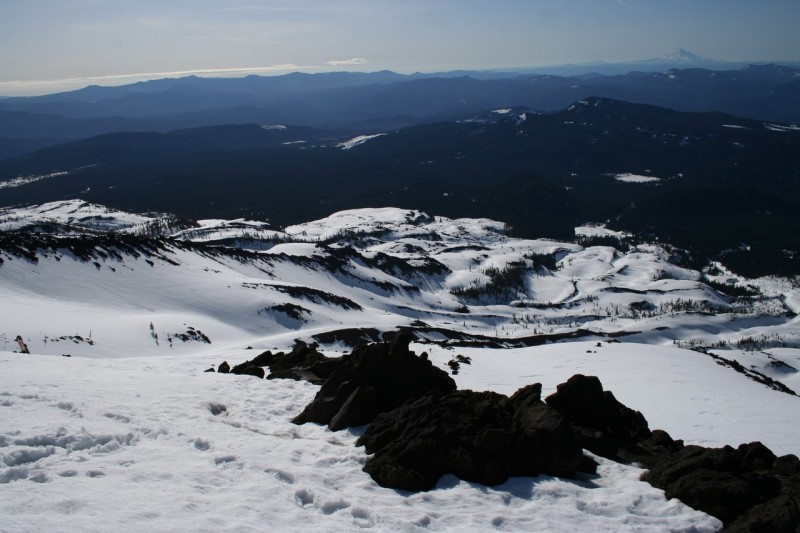looking down the snowy slope of mt st helens with some rocky areas in the foreground
