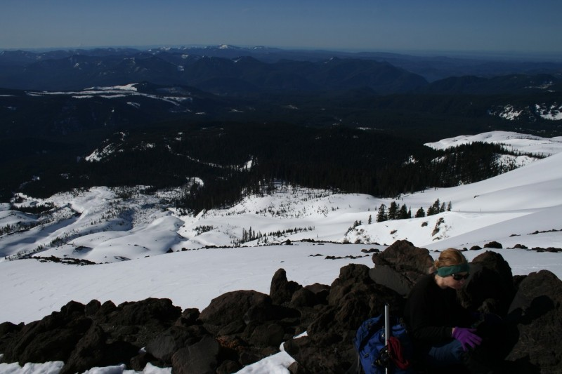 Tasha resting on the rocks in the foreground with the snowy slope of mt st helens in the backgound