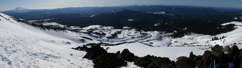 panoramic view of the snowy slope of mt st helens (looking down the mountain) with a rocky section in the foreground