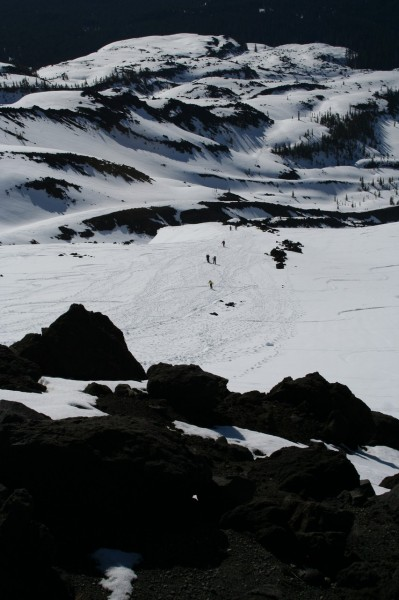 portrait orientation shot of hikers in the distance coming up the snowy slope of mt st helens with a rocky area in the foreground