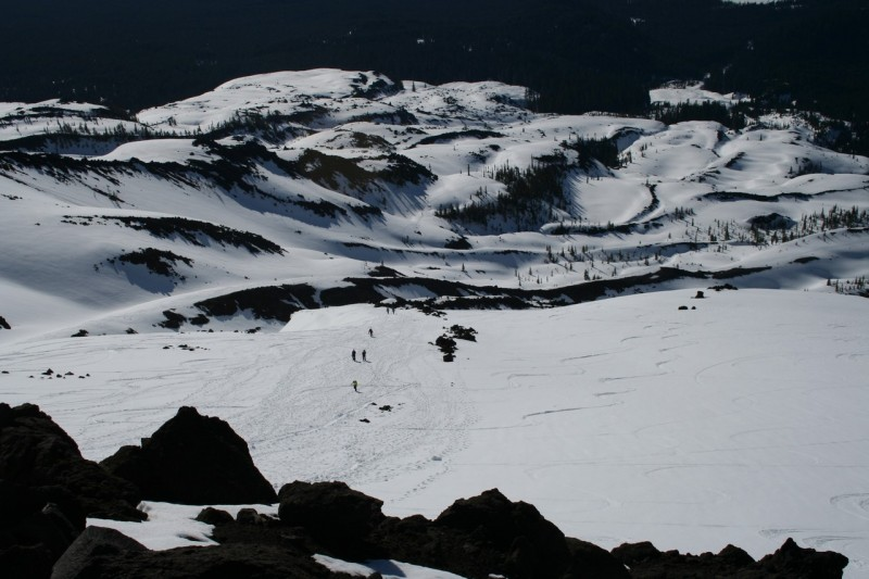 landscape orientation shot of hikers in the distance coming up the snowy slope of mt st helens with a rocky area in the foreground