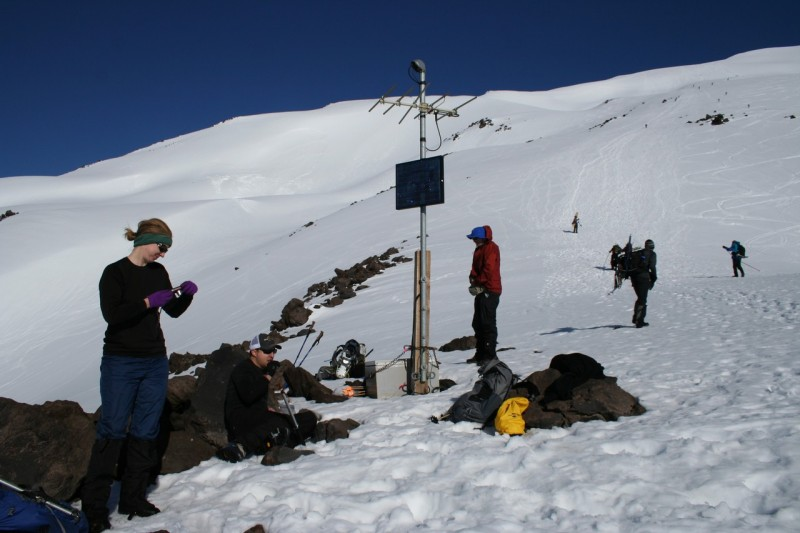 from left to right, tasha standing, troy sitting by the rocks, a pole with a solar panel and an antenna on it and some other hikers, looking up toward the top of mt st helens
