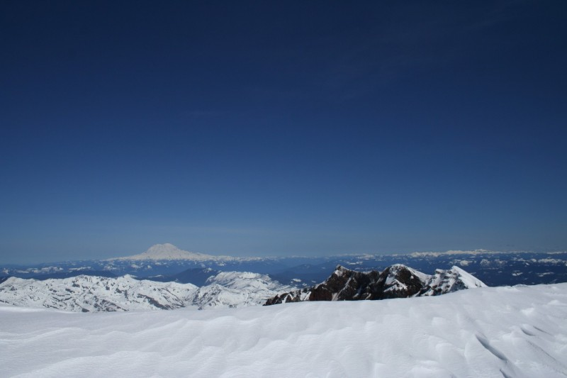 the snowy rim of mt st helens with mt rainier and the sky in the background